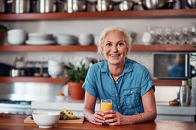 Buy stock photo Cropped portrait of an attractive senior woman enjoying a glass of orange juice while preparing breakfast in the kitchen