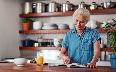 Buy stock photo Cropped shot of an attractive senior woman reading from a recipe book while preparing breakfast in the kitchen