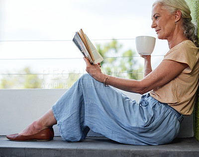 Buy stock photo Full length shot of an attractive senior woman enjoying a cup of coffee while reading a book outside on her balcony at home