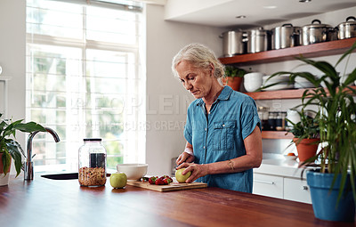 Buy stock photo Cropped shot of an attractive senior woman chopping up apples and other fruit while preparing breakfast in the kitchen