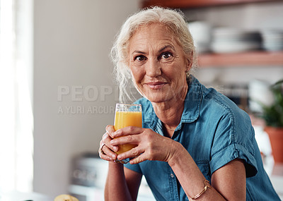 Buy stock photo Cropped portrait of an attractive senior woman enjoying a glass of orange juice while standing in her kitchen at home