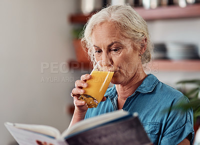 Buy stock photo Cropped shot of an attractive senior woman enjoying a glass of orange while reading a book in her kitchen at home