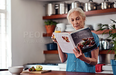 Buy stock photo Cropped shot of an attractive senior woman reading from a recipe book while preparing breakfast in the kitchen at home