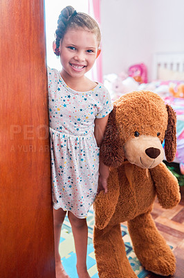 Buy stock photo Portrait of an adorable little girl holding a teddybear and opening the door of her bedroom