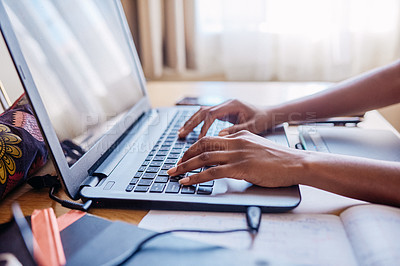 Buy stock photo Cropped shot of an unrecognizable female university student using a laptop while studying in her room