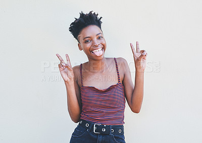 Buy stock photo Cropped portrait of an attractive young female university student showing the peace sign while standing against a grey background