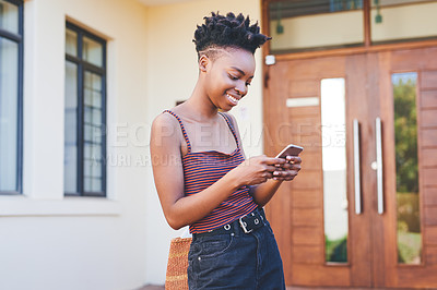 Buy stock photo Cropped shot of an attractive young female university student smiling while using a smartphone outside her residence