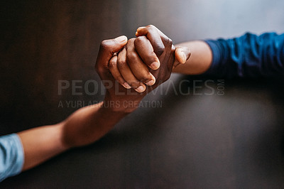 Buy stock photo High angle shot of two unrecognizable people holding hands over a table