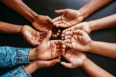 Buy stock photo High angle shot of a group of unrecognizable people holding their hands open together over a table