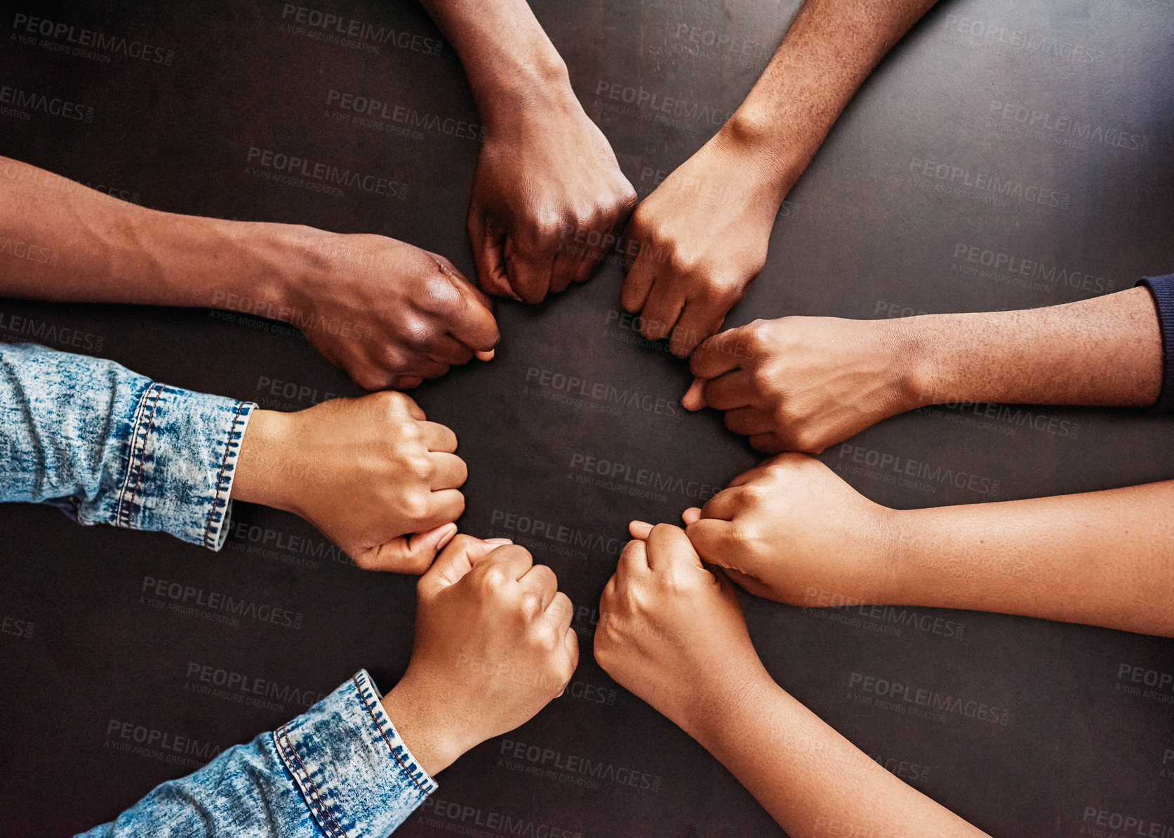 Buy stock photo High angle shot of a group of unrecognizable people holding their fists closed together in a circle on top of a table