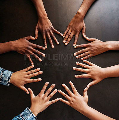 Buy stock photo High angle shot of a group of unrecognizable people holding their hands open in a circle showing the back side of their hands on a table
