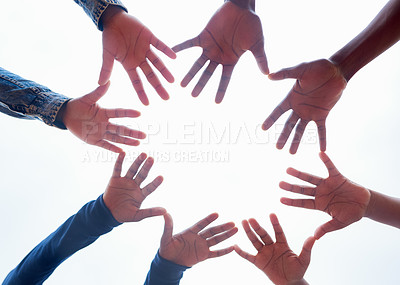 Buy stock photo Low angle shot of a group of unrecognizable people forming a huddle with their hands outside during the day