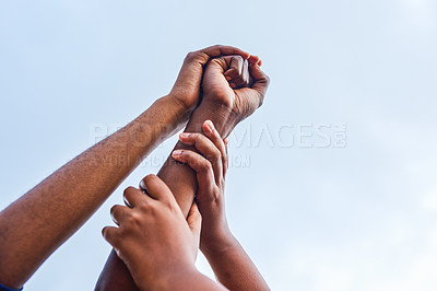 Buy stock photo Cropped shot of a group of unrecognizable people lifting someone's hand in the air outside during the day