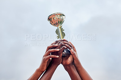 Buy stock photo Cropped shot of a group of unrecognizable people holding up a trophy together in the air outside during the day