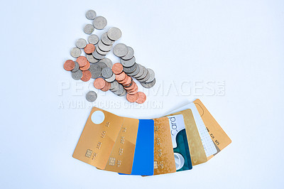 Buy stock photo High angle shot of a collection of credit cards placed next to a heap of coins on top of a white surface inside during the day