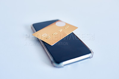 Buy stock photo Closeup of a credit card placed on top of a cellphone while both rest on top of a white surface