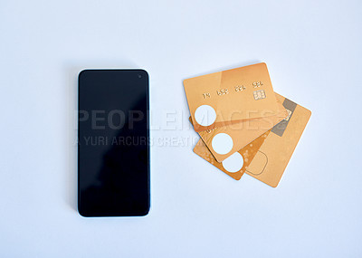 Buy stock photo Closeup of a collection of credit cards placed next to a cellphone on top of a white surface