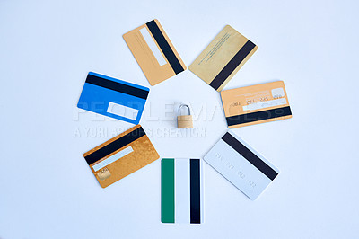 Buy stock photo High angle shot of a collection of credit cards placed in a circle with a lock in the middle on top of a white surface