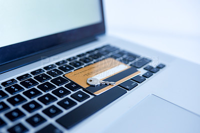 Buy stock photo Closeup of a credit card placed next to a key while both rest on top of a laptop inside during the day