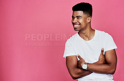 Buy stock photo Cropped shot of a handsome young man standing alone with his arms folded against a pink background in the studio