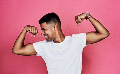 Buy stock photo Cropped shot of a handsome young man standing alone and flexing his biceps against a pink background in the studio