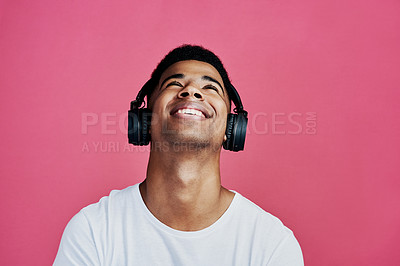 Buy stock photo Cropped shot of a handsome young man standing alone and listening to music through headphones against a pink studio background