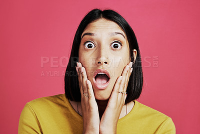 Buy stock photo Cropped portrait of an attractive young female standing alone and looking shocked against a pink background in the studio