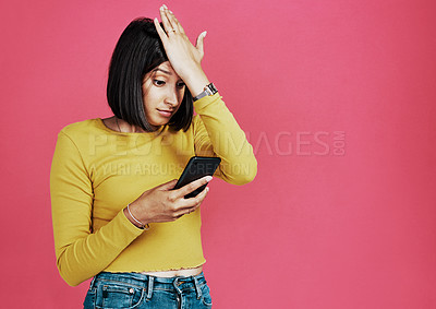 Buy stock photo Cropped shot of an attractive young woman standing alone and feeling stressed while using her cellphone against a pink background