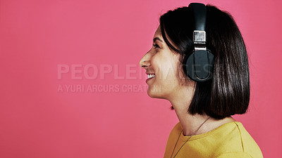 Buy stock photo Cropped shot of an attractive young woman standing alone and listening to music through headphones against a pink studio background