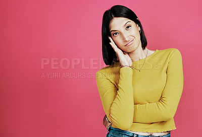 Buy stock photo Cropped portrait of an attractive young woman standing alone and looking confused against a pink background in the studio