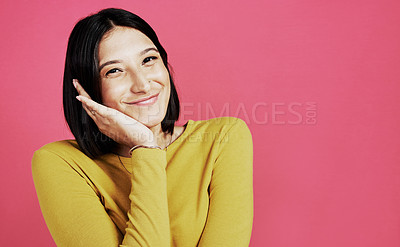 Buy stock photo Cropped portrait of an attractive young woman standing alone against a pink background in the studio