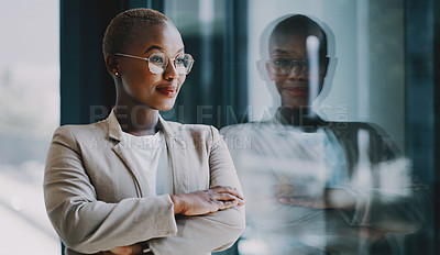 Buy stock photo Shot of a confident young businesswoman looking thoughtfully out the window in an office