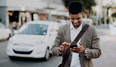 Buy stock photo Cropped shot of a handsome young businessman using his cellphone while outdoors in the city