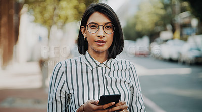Buy stock photo Portrait of an attractive young businesswoman using her cellphone while outdoors in the city