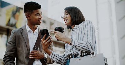 Buy stock photo Cropped shot of two young businesspeople drinking coffee and using a cellphone together outdoors in the city