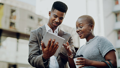 Buy stock photo Cropped shot of two young businesspeople drinking coffee and using a digital tablet together outdoors in the city