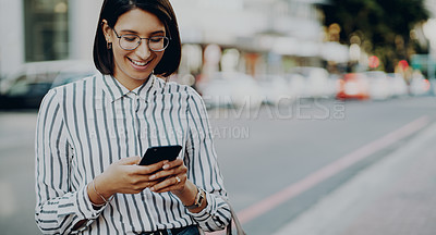 Buy stock photo Cropped shot of an attractive young businesswoman using her cellphone while outdoors in the city