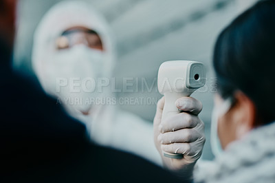 Buy stock photo Shot of a young woman getting her temperature taken with an infrared thermometer by a healthcare worker during an outbreak