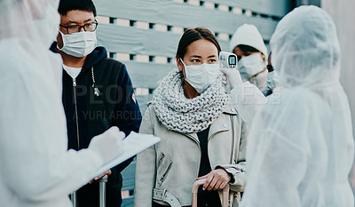 Buy stock photo Shot of a young woman talking to a healthcare worker in a hazmat suit during an outbreak