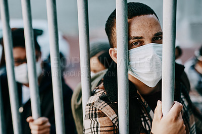 Buy stock photo Shot of a young man wearing a mask while stuck behind a gate in a foreign city