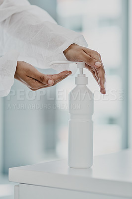 Buy stock photo Cropped shot of a healthcare worker disinfecting herself with hand sanitiser