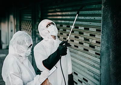 Buy stock photo Shot of two healthcare workers wearing hazmat suits working together to control an outbreak