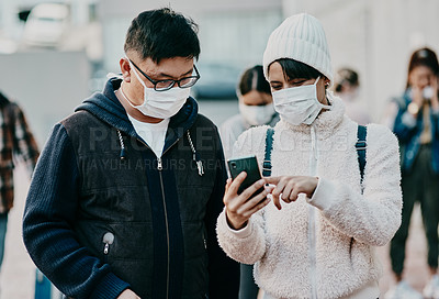 Buy stock photo Shot of a young man and woman using a smartphone and wearing masks while travelling in a foreign city