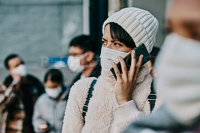 Buy stock photo Shot of a young woman using a smartphone and wearing a mask while travelling in a foreign city