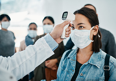 Buy stock photo Shot of a young woman getting her temperature taken with an infrared thermometer by a doctor during an outbreak