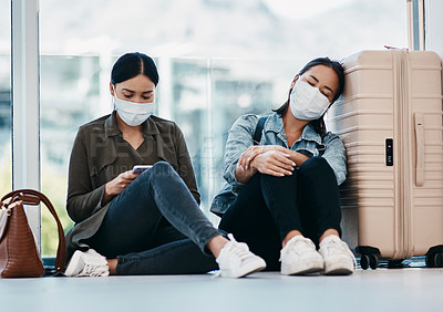 Buy stock photo Shot of two young women wearing masks while waiting together in an airport