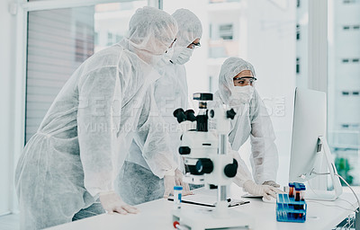 Buy stock photo Shot of a group of scientists in hazmat suits conducting medical research in a laboratory