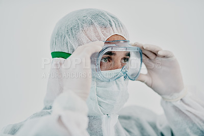 Buy stock photo Shot of a young man putting on his protective gear before the decontamination process