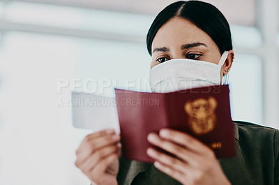 Buy stock photo Shot of a woman wearing a mask and holding her passport in an airport