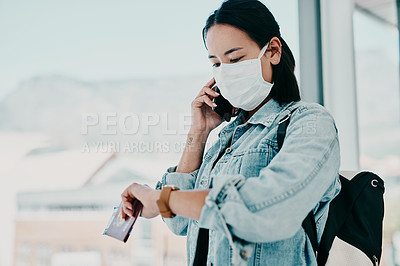 Buy stock photo Shot of a young woman wearing a mask, using a smartphone and checking the time in an airport